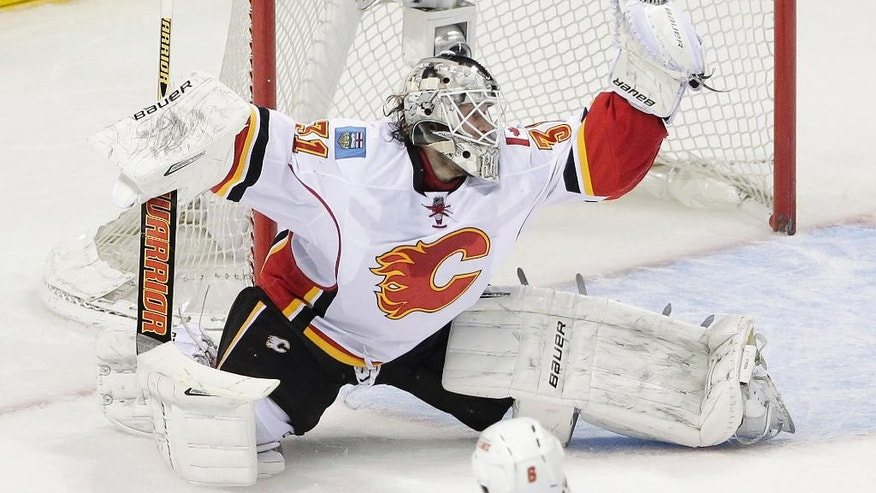 Calgary Flames goalie Karri Ramo, of Finland, stops a shot from the San Jose Sharks during the second period of an NHL hockey game Wednesday, Nov. 26, 2014, in San Jose, Calif. (AP Photo/Marcio Jose Sanchez)