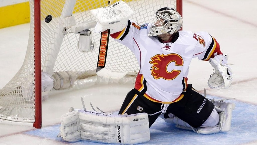 Calgary Flames goalie Karri Ramo, of Finland, deflects a San Jose Sharks shot during the second period of an NHL hockey game Wednesday, Nov. 26, 2014, in San Jose, Calif. (AP Photo/Marcio Jose Sanchez)