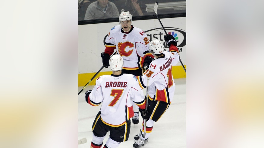 Calgary Flames left wing Jiri Hudler, top, of the Czech Republic, celebrates his goal against the San Jose Sharks with teammates Johnny Gaudreau (13) and T.J. Brodie (7) during the second period of an NHL hockey game Wednesday, Nov. 26, 2014, in San Jose, Calif. (AP Photo/Marcio Jose Sanchez)