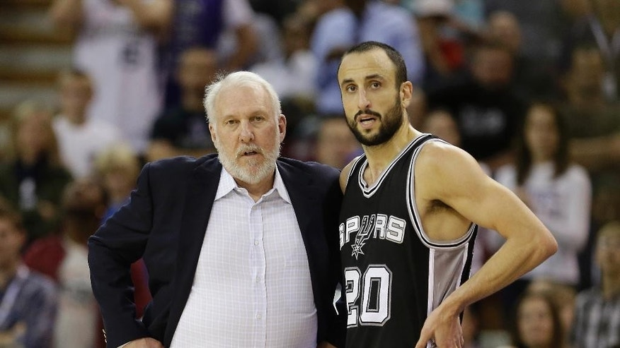 FILE - In this Nov. 15, 2014, file photo, San Antonio Spurs head coach Gregg Popovich talks with Spurs guard Manu Ginobili during the second half of an NBA basketball game against the Sacramento Kings in Sacramento, Calif. Their first days together were difficult, but Ginobili and Popovich eventually found common ground. In doing so, they made each other, and the San Antonio Spurs, so much better. (AP Photo/Rich Pedroncelli, File)