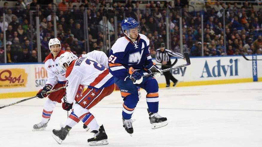 New York Islanders center Frans Nielsen (51) leaps past Washington Capitals center Jay Beagle (83) and defenseman Matt Niskanen (2) to chase the puck in the second period of an NHL hockey game at Nassau Coliseum on Wednesday, Nov. 26, 2014, in Uniondale, N.Y. (AP Photo/Kathy Kmonicek)