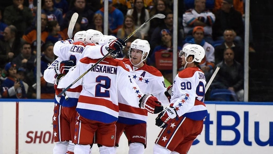 Washington Capitals left wing Alex Ovechkin (8) celebrates his goal against the New York Islanders with defenseman Matt Niskanen (2), center Nicklas Backstrom (19) and left wing Marcus Johansson (90) in the second period of an NHL hockey game at Nassau Coliseum on Wednesday, Nov. 26, 2014, in Uniondale, N.Y. (AP Photo/Kathy Kmonicek)