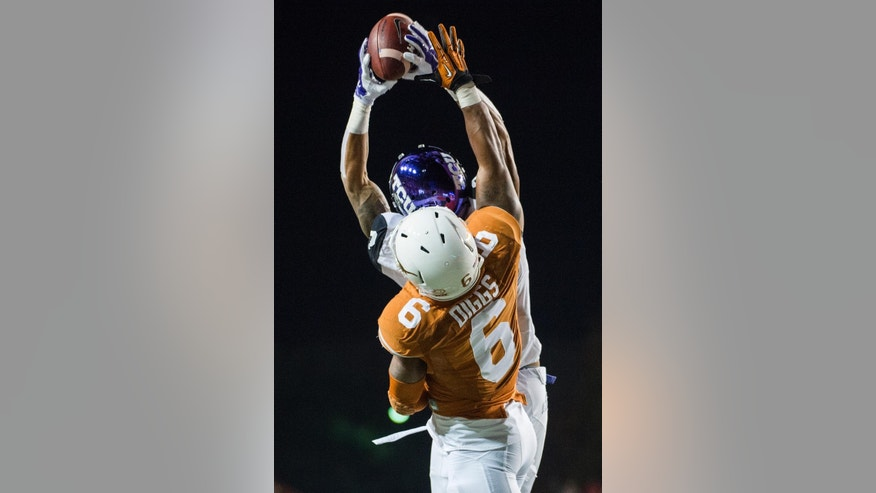 TCU's Josh Doctson, top, catches a pass near the end zone while Texas' Quandre Diggs (6) defends during the first half of an NCAA college football game, Thursday, Nov. 27, 2014, in Austin, Texas. (AP Photo/Ashley Landis)
