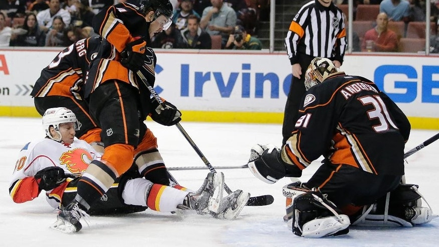 Calgary Flames' Markus Granlund, left, of Finland, falls to the ice as he is defended by Anaheim Ducks' Cam Fowler in front of Ducks goalie Frederik Andersen, right, of Denmark, during the first period of an NHL hockey game Tuesday, Nov. 25, 2014, in Anaheim, Calif. (AP Photo/Jae C. Hong)