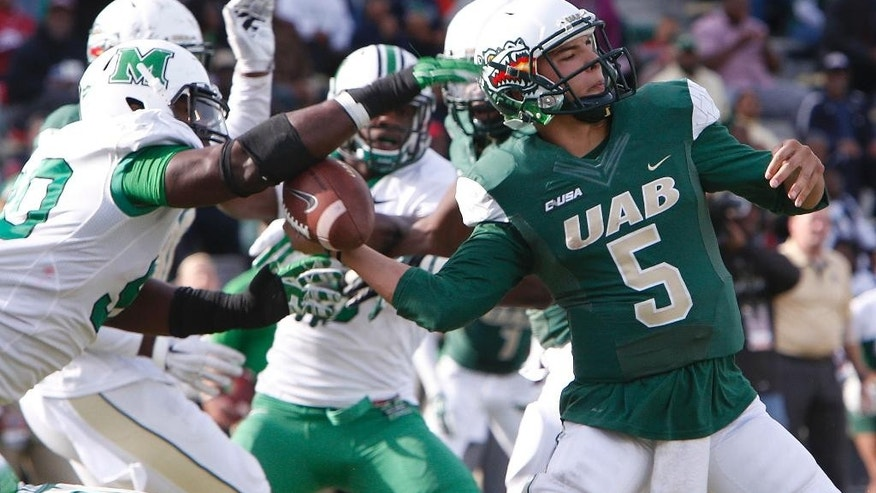 Marshall defensive lineman Arnold Blackmon, left, knocks the ball away from UAB quarterback Cody Clements (5) for a fumble in the end zone during the fourth quarter of an NCAA college football game, Saturday, Nov. 22, 2014, in Birmingham, Ala. Marshall's Ra'shawde Myers recovered a fumble and won 23-18. (AP Photo/The Herald-Dispatch, Hal Yeager)