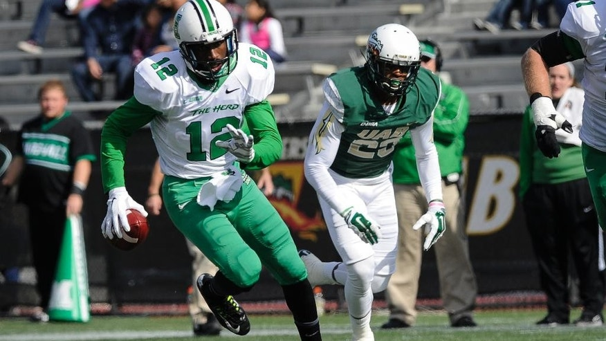 Marshall quarterback Rakeem Cato (12) scrambles for yardage in front of UAB linebacker Tevin Crews (23) during the first quarter of an NCAA college football game, Saturday, Nov. 22, 2014, in Birmingham, Ala. Marshall won 23-18. (AP Photo/John Amis)