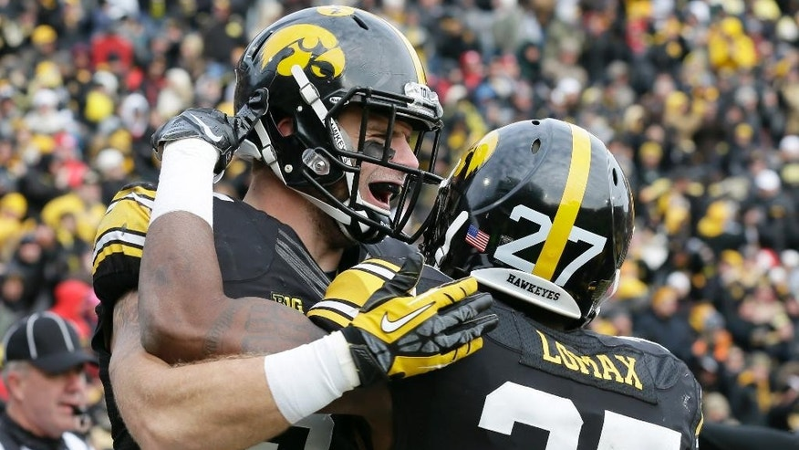 Iowa defensive back John Lowdermilk, left, celebrates with teammate Jordan Lomax after returning an interception for a touchdown during the first half of an NCAA college football game against Nebraska, Friday, Nov. 28, 2014, in Iowa City, Iowa. (AP Photo/Charlie Neibergall)
