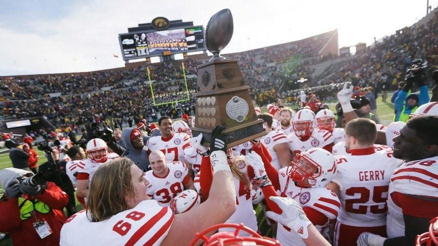 Nebraska players celebrate with the Heroes Trophy after their 37-34 overtime victory over Iowa in an NCAA college football game, Friday, Nov. 28, 2014, in Iowa City, Iowa. (AP Photo/Charlie Neibergall)