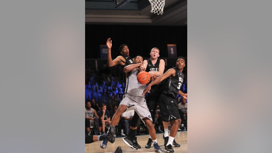 Georgetown's Mikael Hopkins fights for a rebound with a trio of Butler players during their third game in the Battle 4 Atlantis basketball tournament in Paradise Island, Bahamas, Friday, Nov. 28, 2014. (AP Photo/Tim Aylen)