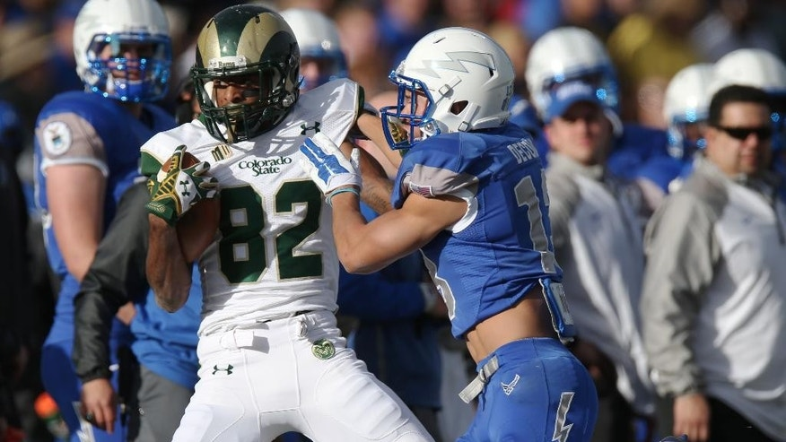 Colorado State wide receiver Rashard Higgins, left, is stopped by Air Force defensive back Justin DeCoud after making a catch in the first quarter of an NCAA college football game at Air Force Academy, Colo., on Friday, Nov. 28, 2014. (AP Photo/David Zalubowski)