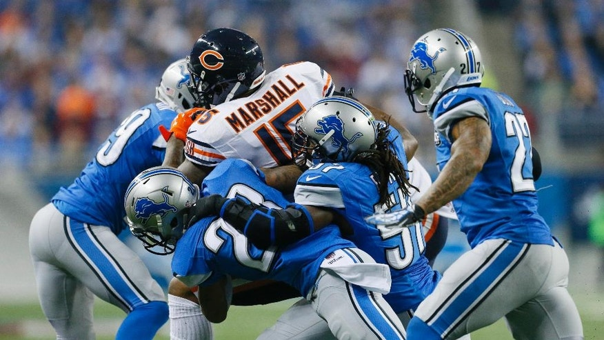 Chicago Bears wide receiver Brandon Marshall (15) is stopped by Detroit Lions cornerback Darius Slay (23) and linebacker Josh Bynes (57) during the second half of an NFL football game in Detroit, Thursday, Nov. 27, 2014. (AP Photo/Rick Osentoski)