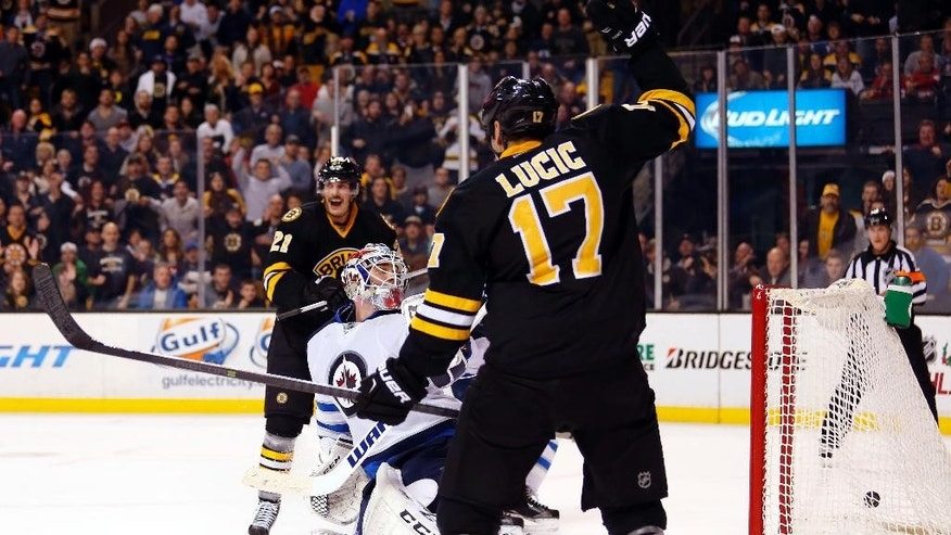 Winnipeg Jets goalie Michael Hutchinson looks back to see Boston Bruins' Dougie Hamilton's shot go in the net during overtime as Boston Bruins' Loui Eriksson and Milan Lucic looks on during the Boston Bruins 2-1 overtime win over the Winnipeg Jets in an NHL hockey game in Boston, Friday, Nov. 28, 2014. (AP Photo/Winslow Townson)
