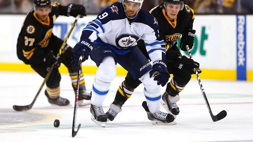 Winnipeg Jets' Evander Kane (9) keeps the puck away from David Pastrnak during the Boston Bruins 2-1 overtime win over the Winnipeg Jets in an NHL hockey game in Boston, Friday, Nov. 28, 2014. (AP Photo/Winslow Townson)