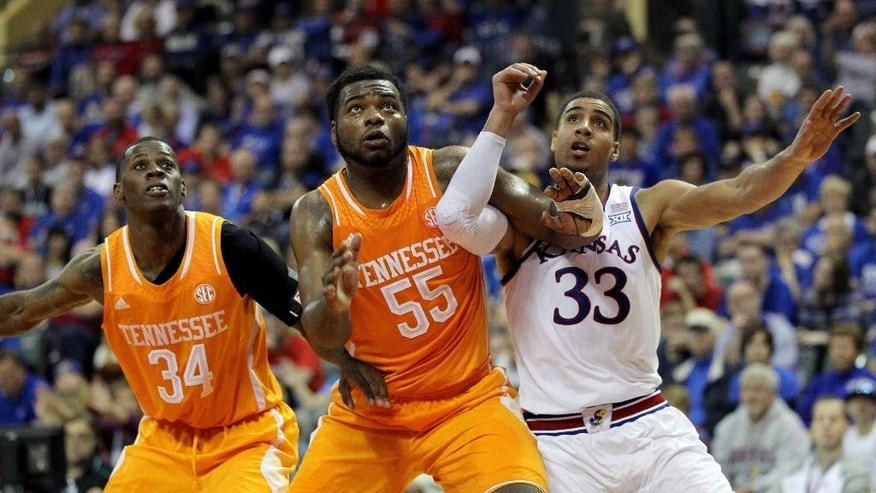 Kansas forward Landen Lucas (33) fights for a rebound with Tennessee forward Dominic Woodson (55) and guard Devon Baulkman (34) during the first half of an NCAA college basketball game in Lake Buena Vista, Fla., Friday, Nov. 28, 2014. (AP Photo/Reinhold Matay)