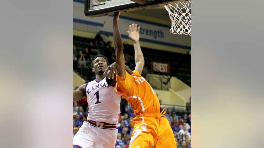 Tennessee guard Josh Richardson is fouled by Kansas guard Wayne Selden Jr. (1) during the first half of an NCAA college basketball game in Lake Buena Vista, Fla., Friday, Nov. 28, 2014. (AP Photo/Reinhold Matay)