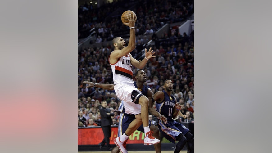 Portland Trail Blazers forward Nicolas Batum, from France, left, drives to the hoop past Memphis Grizzlies guard Mike Conley, right, and forward Tony Allen during the first half of an NBA basketball game in Portland, Ore., Friday, Nov. 28, 2014.(AP Photo/Don Ryan)