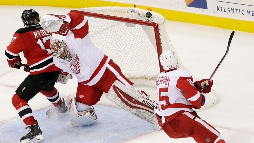 Detroit Red Wings goalie Petr Mrazek, center, of the Czech Republic, makes a save as teammate Riley Sheahan, right, helps defend against New Jersey Devils right wing Michael Ryder (17) during the third period of an NHL hockey game, Friday, Nov. 28, 2014, in Newark, N.J. The Red Wings won 5-4 in a shootout. (AP Photo/Julio Cortez)