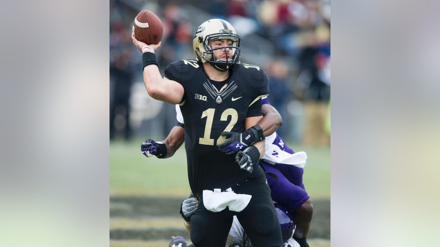 Purdue's Austin Appleby (12) tries to release his pass as he's hit in the backfield by Northwestern's Matthew Harris (27) during the second half of an NCAA college football game, Saturday, Nov. 22, 2014, in West Lafayette, Ind. Northwestern defeated Purdue 38-14. (AP Photo/Doug McSchooler)
