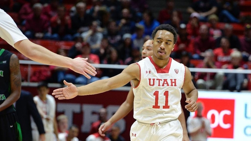 Utah guard Brandon Taylor (11) gets congratulations after a defensive stop during the first half on an NCAA college basketball game, Friday, Nov. 28, 2014 in Salt Lake City. (AP Photo/The Salt Lake Tribune, Scott Sommerdorf)  DESERET NEWS OUT; LOCAL TELEVISION OUT; MAGS OUT