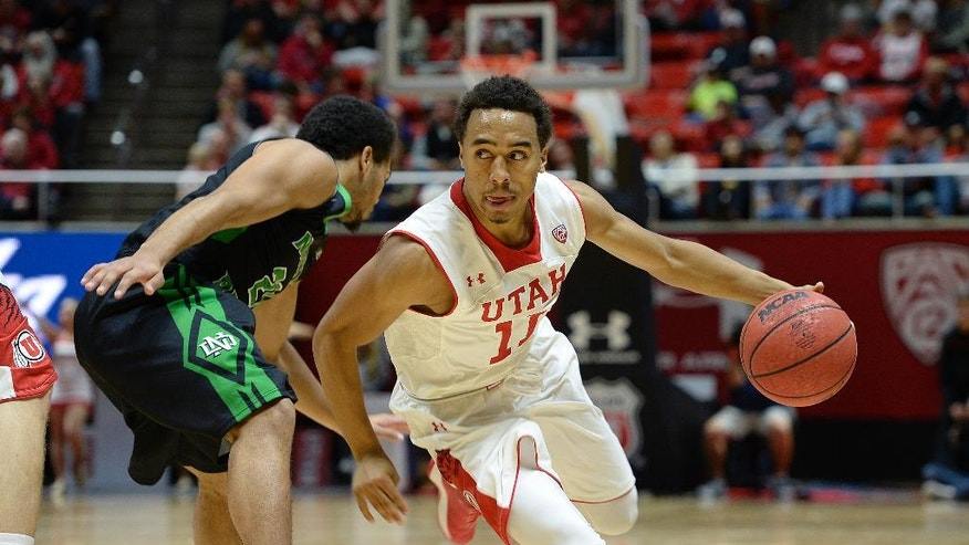 Utah guard Brandon Taylor (11) drives against North Dakota guard Quinton Hooker (21) during the first half on an NCAA college basketball game, Friday, Nov. 28, 2014 in Salt Lake City. (AP Photo/The Salt Lake Tribune, Scott Sommerdorf)  DESERET NEWS OUT; LOCAL TELEVISION OUT; MAGS OUT
