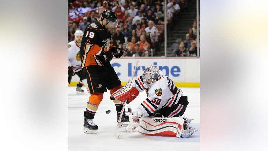 Chicago Blackhawks goalie Corey Crawford, right, stops a shot as Anaheim Ducks' Patrick Maroon watches during the second period of an NHL hockey game Friday, Nov. 28, 2014, in Anaheim, Calif. (AP Photo/Jae C. Hong)