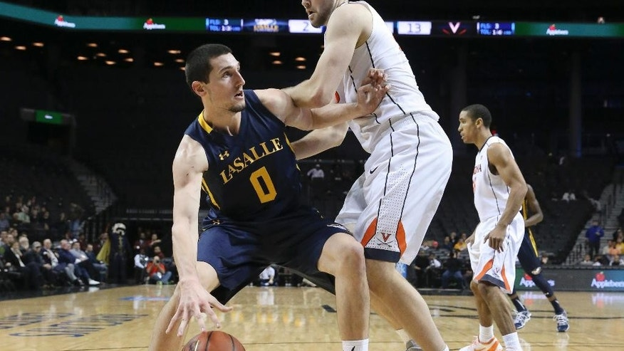 La Salle center Steve Zack (0) looks to pass around Virginia forward/center Mike Tobey (10) in the first half of their NCAA college basketball game during the Barclays Center Classic, Friday, Nov. 28, 2014, in New York. (AP Photo/John Minchillo)