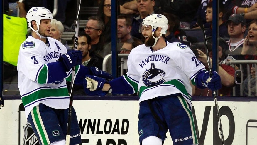 Vancouver Canucks' Chris Higgins, right, celebrates his goal against the Columbus Blue Jackets with teammate Kevin Bieksa  during the second period of an NHL hockey game in Columbus, Ohio, Friday, Nov. 28, 2014. Vancouver won 5-0.(AP Photo/Paul Vernon)