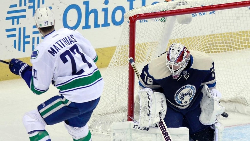 Vancouver Canucks' Shawn Matthias, left, scores against Columbus Blue Jackets goalie Sergei Bobrovosky, of Russia, during the third period of an NHL hockey game in Columbus, Ohio, Friday, Nov. 28, 2014. (AP Photo/Paul Vernon)