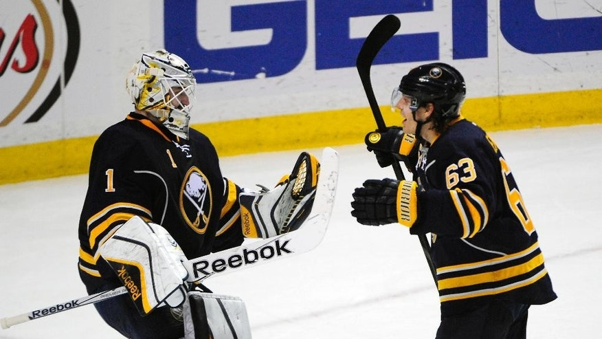 Buffalo Sabres goaltender Jhonas Enroth (1), of Sweden, celebrates with center Tyler Ennis (63) after the third period of an NHL hockey game against the Montreal Canadiens Friday, Nov. 28, 2014, in Buffalo, N.Y. Buffalo won 2-1. (AP Photo/Gary Wiepert)