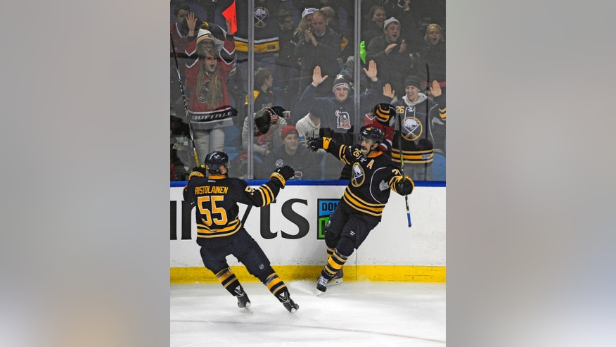 Buffalo Sabres' Rasmus Ristolainen (55) celebrates the game winning goal by Matt Moulson (26) in front of their fans during the third period of an NHL hockey game against the Montreal Canadiens Friday, Nov. 28, 2014, in Buffalo, N.Y.  Buffalo won 2-1. (AP Photo/Gary Wiepert)
