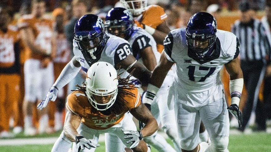 Texas' Marcus Johnson (7) reaches to recover a fumble during the second half of an NCAA college football game against TCU, Thursday, Nov. 27, 2014, in Austin, Texas. TCU's Derrick Kindred (26) and Sam Carter (17) defend. (AP Photo/Ashley Landis)