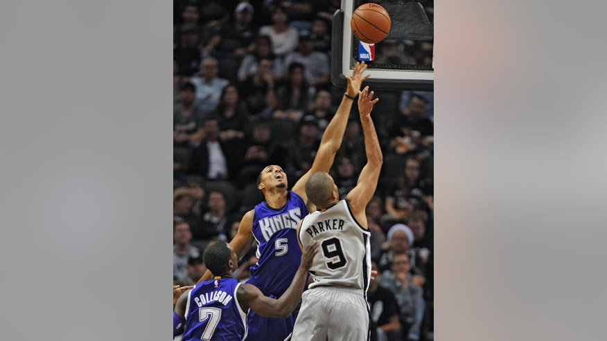 San Antonio Spurs guard Tony Parker, right, of France, shoots against Sacramento Kings center Ryan Hollins and Kings guard Darren Collison, left, during the first half of an NBA basketball game, Friday, Nov. 28, 2014, in San Antonio. (AP Photo/Darren Abate)