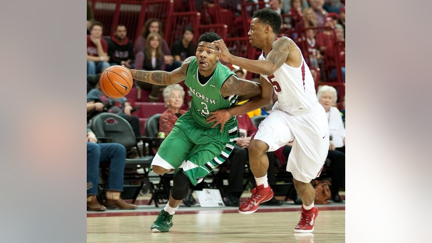 North Texas' DeAndre Harris (3) drives the ball to the hoop as Arkansas' Anthlon Bell (5) defends in the first half of an NCAA college basketball game in Fayetteville, Ark., Friday, Nov. 28, 2014. (AP Photo/Sarah Bentham)