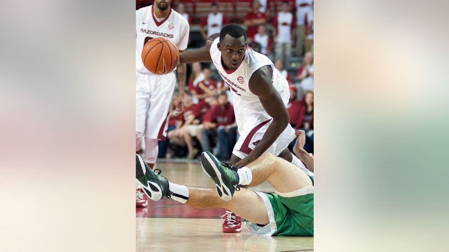 Arkansas' Alandise Harris (2) drives the ball over the legs of North Texas' Colin Voss (33) in the first half of an NCAA college basketball game in Fayetteville, Ark., Friday, Nov. 28, 2014. (AP Photo/Sarah Bentham)