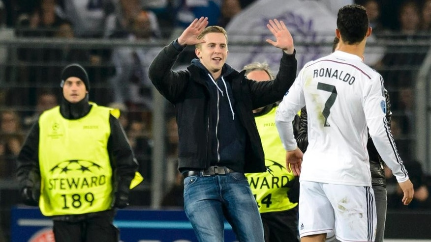 In this picture taken Wednesday, Nov. 26, 2014, fans run in the pitch next to Madrid's Cristiano Ronaldo, right, during an UEFA Champions League group B soccer match between Switzerland's FC Basel 1893 and Spain's Real Madrid CF in the St. Jakob-Park stadium in Basel, Switzerland. UEFA has charged Basel after fans got close to Real Madrid star Cristiano Ronaldo on the pitch during a Champions League match. Five spectators encroached on the pitch from different sections of the St-Jakob Park stadium in the 89th minute of Madrid's 1-0 win. (AP Photo/Keystone, Laurent Gillieron)
