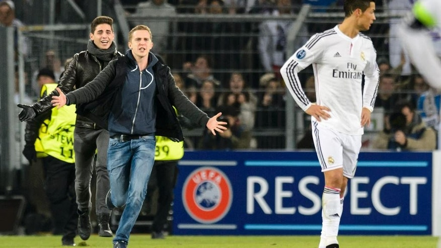 In this picture taken Wednesday, Nov. 26, 2014, fans run on the pitch next to Madrid's Cristiano Ronaldo, right, during an UEFA Champions League group B match between Switzerland's FC Basel 1893 and Spain's Real Madrid CF in the St. Jakob-Park stadium in Basel, Switzerland. UEFA has charged Basel after fans got close to Real Madrid star Cristiano Ronaldo on the pitch during a Champions League match. Five spectators encroached on the pitch from different sections of the St-Jakob Park stadium in the 89th minute of Madrid's 1-0 win. (AP Photo/Keystone, Laurent Gillieron)