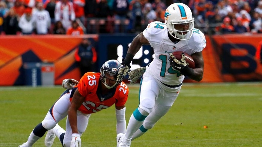Miami Dolphins wide receiver Jarvis Landry (14) breaks free from Denver Broncos cornerback Chris Harris (25) during the first half of an NFL football game, Sunday, Nov. 23, 2014, in Denver. (AP Photo/Jack Dempsey)