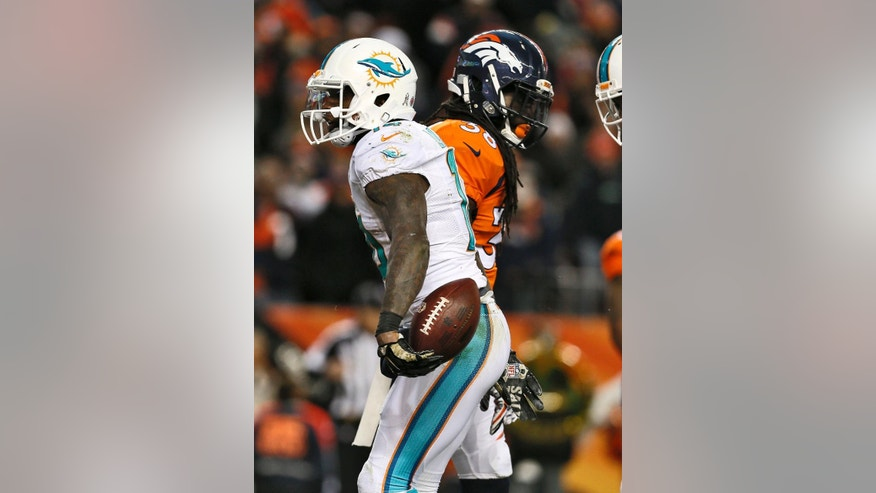 Miami Dolphins wide receiver Jarvis Landry, front, celebrates his touchdown as Denver Broncos strong safety Quinton Carter walks away during the second half of an NFL football game, Sunday, Nov. 23, 2014, in Denver. (AP Photo/Joe Mahoney)