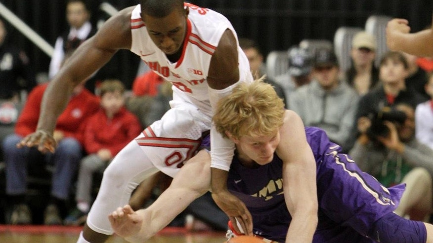 James Madison's Paulius Satkus, right, and Ohio State's Shannon Scott chase a loose ball during the first half of an NCAA college basketball game Friday, Nov. 28, 2014, in Columbus, Ohio. (AP Photo/Jay LaPrete)