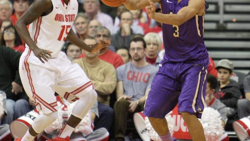 James Madison's Winston Grays, right, passes the ball as Ohio State's Kam Williams defends during the first half of an NCAA college basketball game Friday, Nov. 28, 2014, in Columbus, Ohio. (AP Photo/Jay LaPrete)