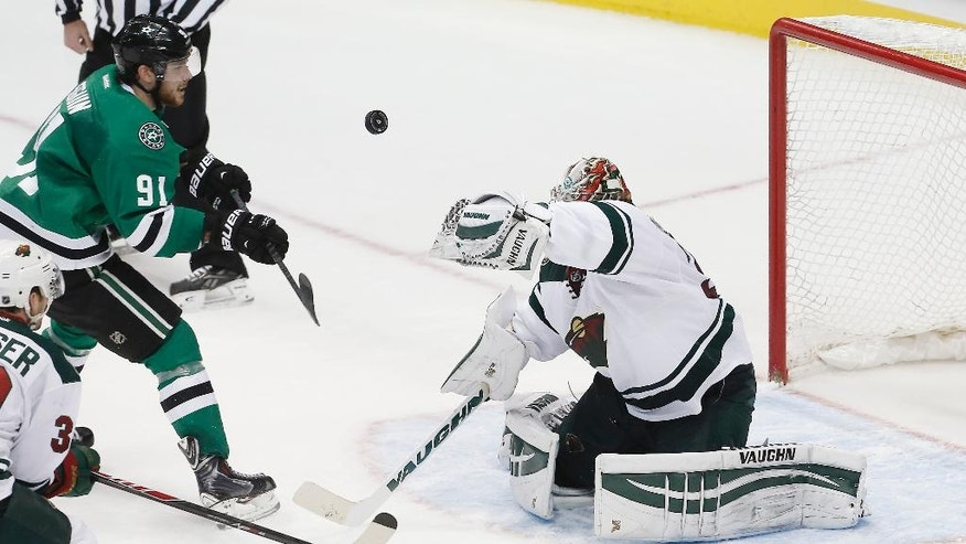 Dallas Stars forward Tyler Seguin (91) shoots the puck past Minnesota Wild goalie Darcy Kuemper (35) for a goal in the second period of an NHL hockey game, Friday, Nov. 28, 2014, in Dallas. (AP Photo/Brandon Wade)