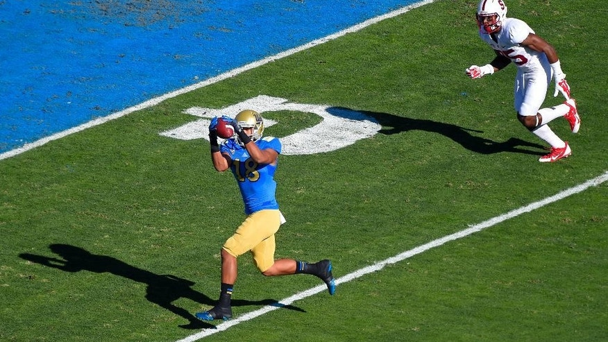 UCLA wide receiver Thomas Duarte makes a touchdown catch as Stanford cornerback Alex Carter defends during the first half of an NCAA college football game, Friday, Nov. 28, 2014, in Pasadena, Calif. (AP Photo/Mark J. Terrill)