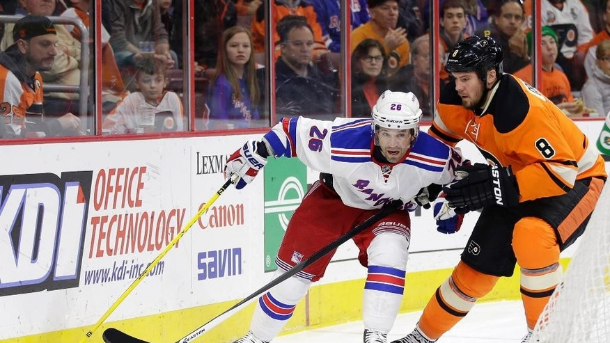 New York Rangers' Martin St. Louis, left, battles with Philadelphia Flyers' Nicklas Grossmann, of Sweden,  for control of the puck during the first period of an NHL hockey game, Friday, Nov. 28, 2014, in Philadelphia. New York won 3-0. (AP Photo/Matt Slocum)