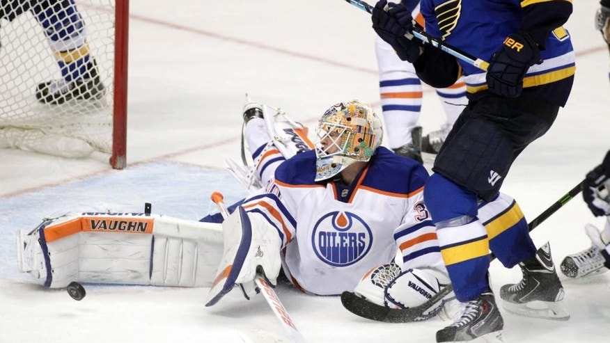Edmonton Oilers goalie Ben Scrivens (30) makes a kick save on a shot from St. Louis Blues' T.J. Oshie (74) in the third period of an NHL hockey game, Friday, Nov. 28, 2014, in St. Louis. The Blues won 4-3 in overtime. (AP Photo/Tom Gannam)