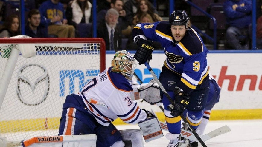 Edmonton Oilers goalie Ben Scrivens, left, trips up St. Louis Blues' Steve Ott (9) in the second period of an NHL hockey game, Friday, Nov. 28, 2014, in St. Louis. (AP Photo/Tom Gannam)