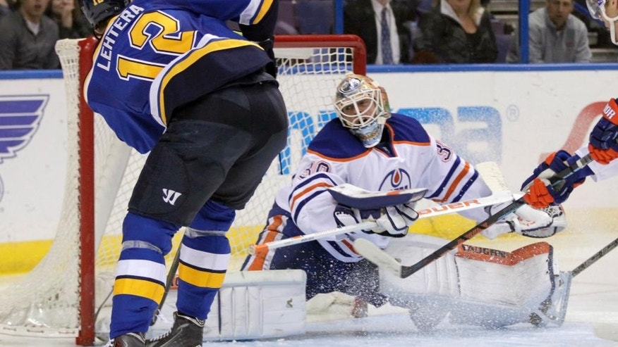 Edmonton Oilers goalie Ben Scrivens (30) stops a shot from St. Louis Blues' Jori Lehtera (12) in the second period of an NHL hockey game, Friday, Nov. 28, 2014, in St. Louis. (AP Photo/Tom Gannam)