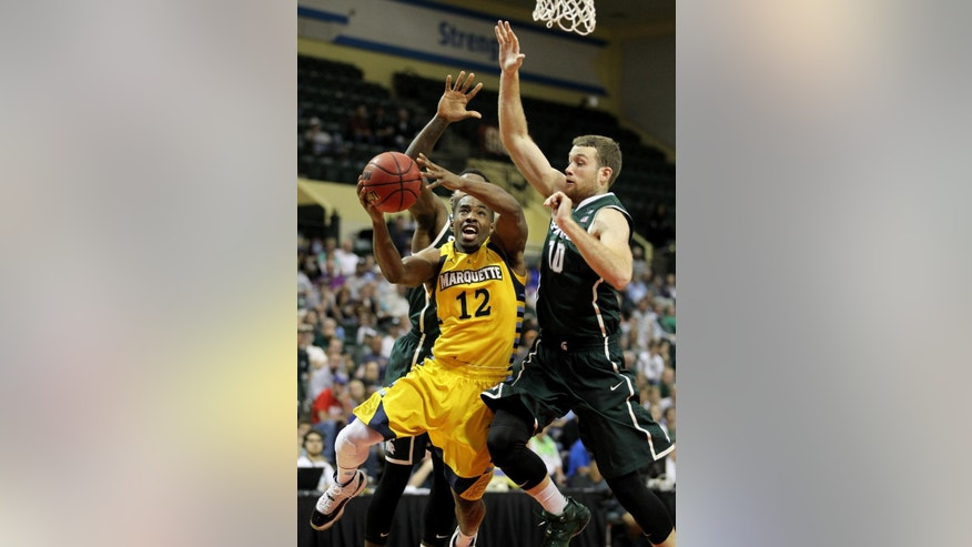 Marquette guard Derrick Wilson (12) is blocked by Michigan State forward Matt Costello (10) and guard Branden Dawson during the second half of an NCAA college basketball game in Lake Buena Vista, Fla., Friday, Nov. 28, 2014. (AP Photo/Reinhold Matay)