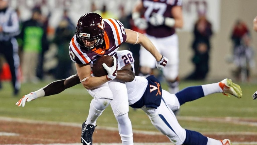 Virginia Tech wide receiver Willie Byrn (82) tries to break the tackle of Virginia safety Wilfred Wahee (28) during the first half of an NCAA college football game in Blacksburg, Va., Friday, Nov. 28, 2014. (AP Photo/Steve Helber)
