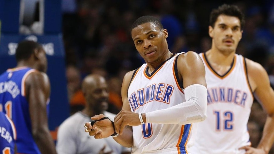 Oklahoma City Thunder guard Russell Westbrook (0) adjusts his hand brace after being awarded a foul shot in the second quarter of an NBA basketball game against the New York Knicks in Oklahoma City, Friday, Nov. 28, 2014. (AP Photo/Sue Ogrocki)