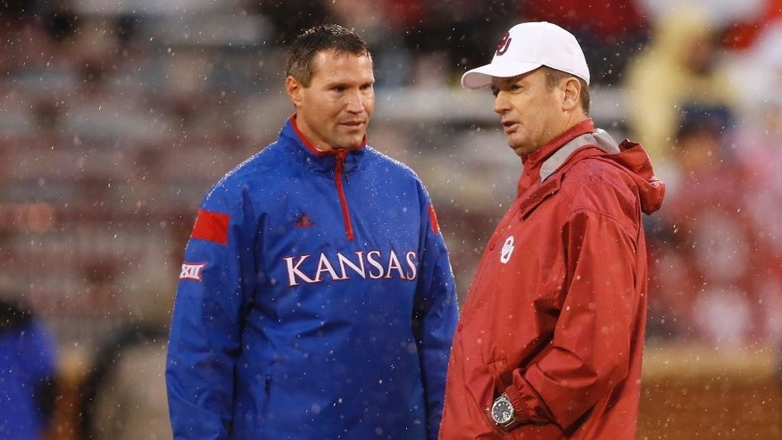 Kansas head coach Clint Bowen, left, and Oklahoma head coach Bob Stoops, right, talk before the start of their weather delayed NCAA college football game in Norman, Okla., Saturday, Nov. 22, 2014.  The start time was pushed back at least 90 minutes due to lightning. (AP Photo/Sue Ogrocki)